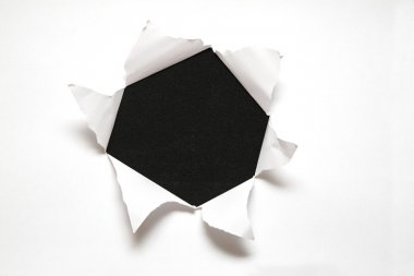 The sheet of paper with the hole against the black background