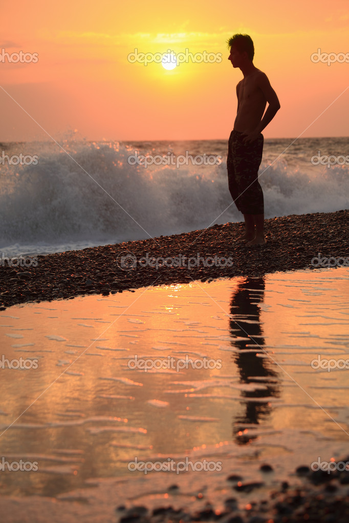 Silhouette guy on sunset wavy beach