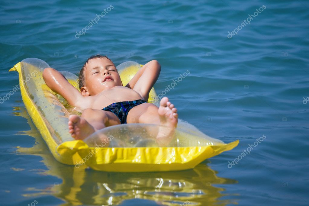 Boy in dark blue swimming trunks relaxing on an inflatable mattr