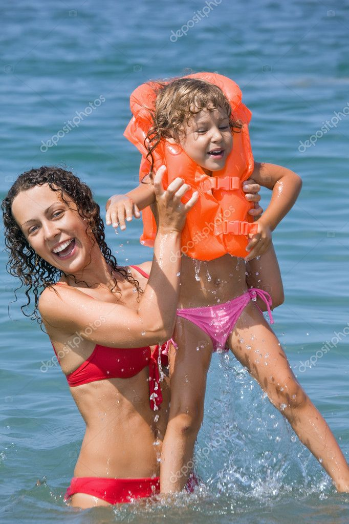 Young woman keeps in hands little girl in lifejackets in sea on