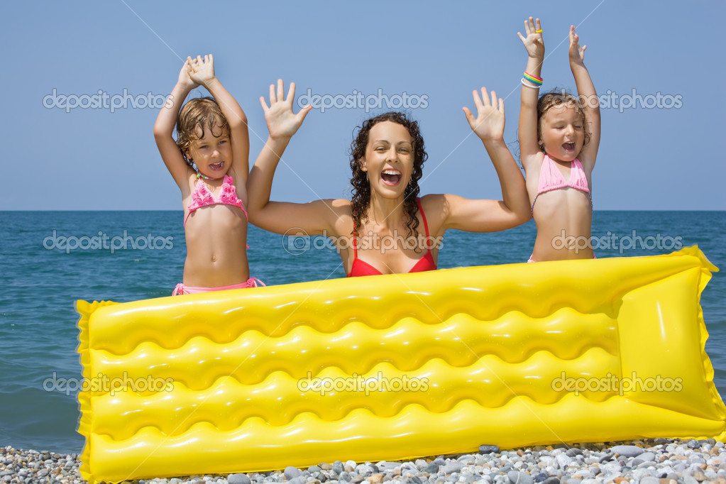 Young woman and two little girls standing behind an inflatable m
