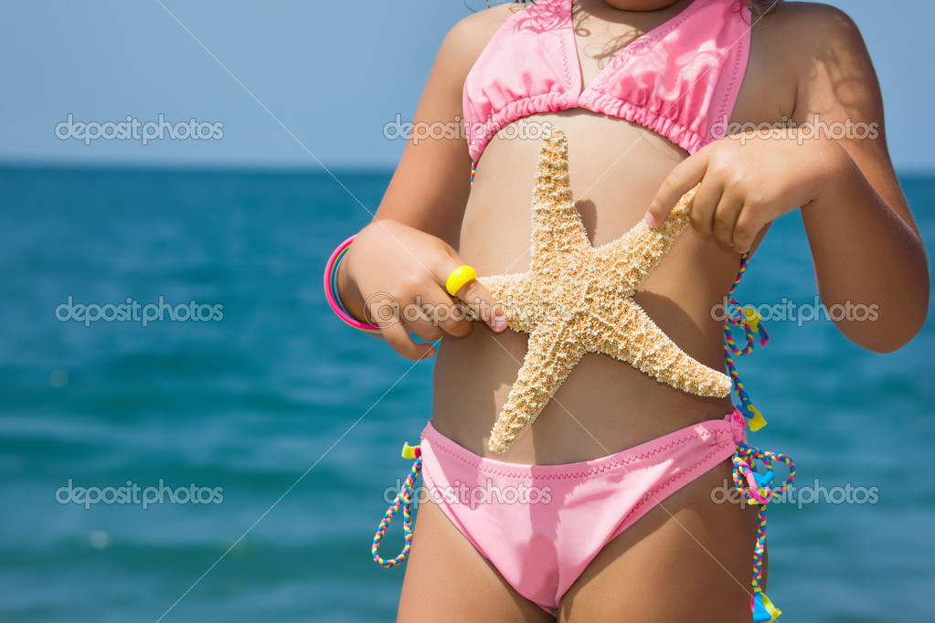 Body of little girl with starfish on beach