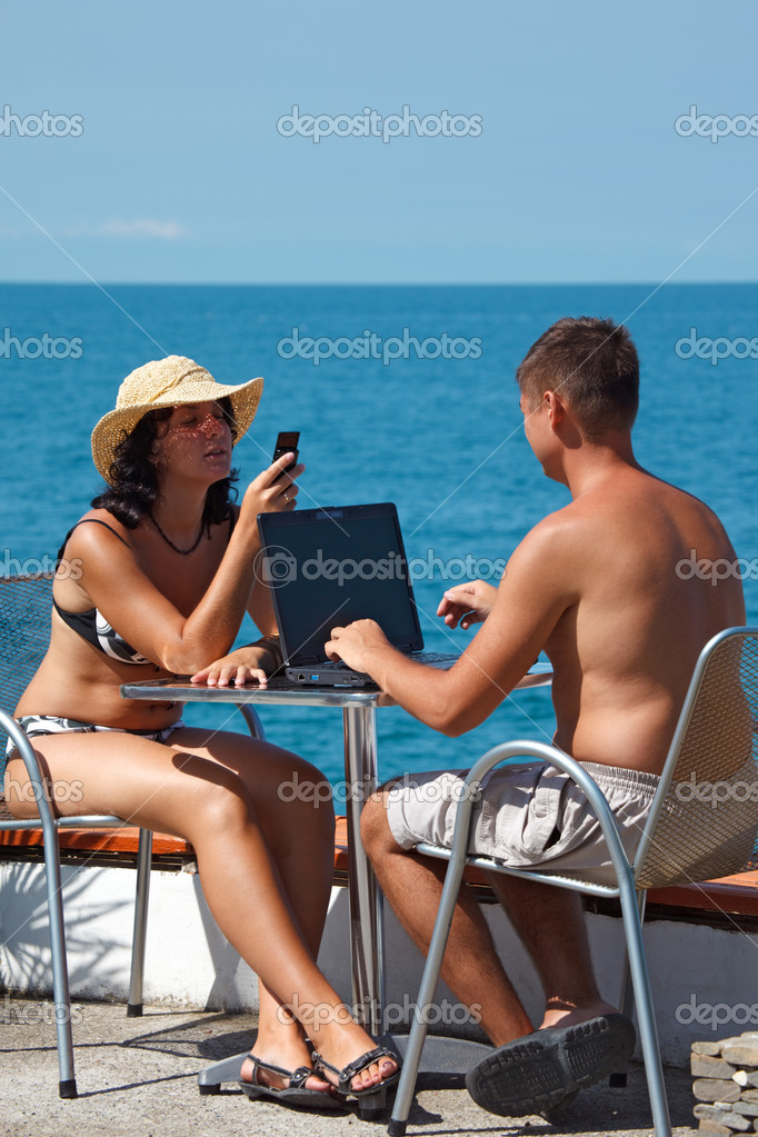 Family resting on sea with laptop