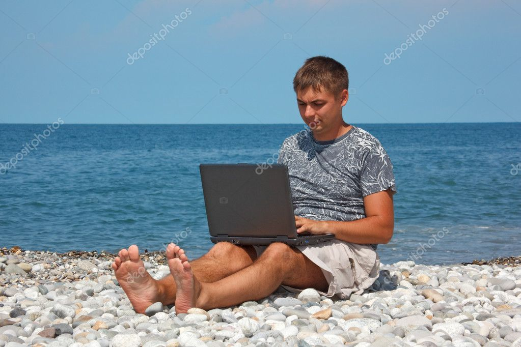 Man on seashore with laptop