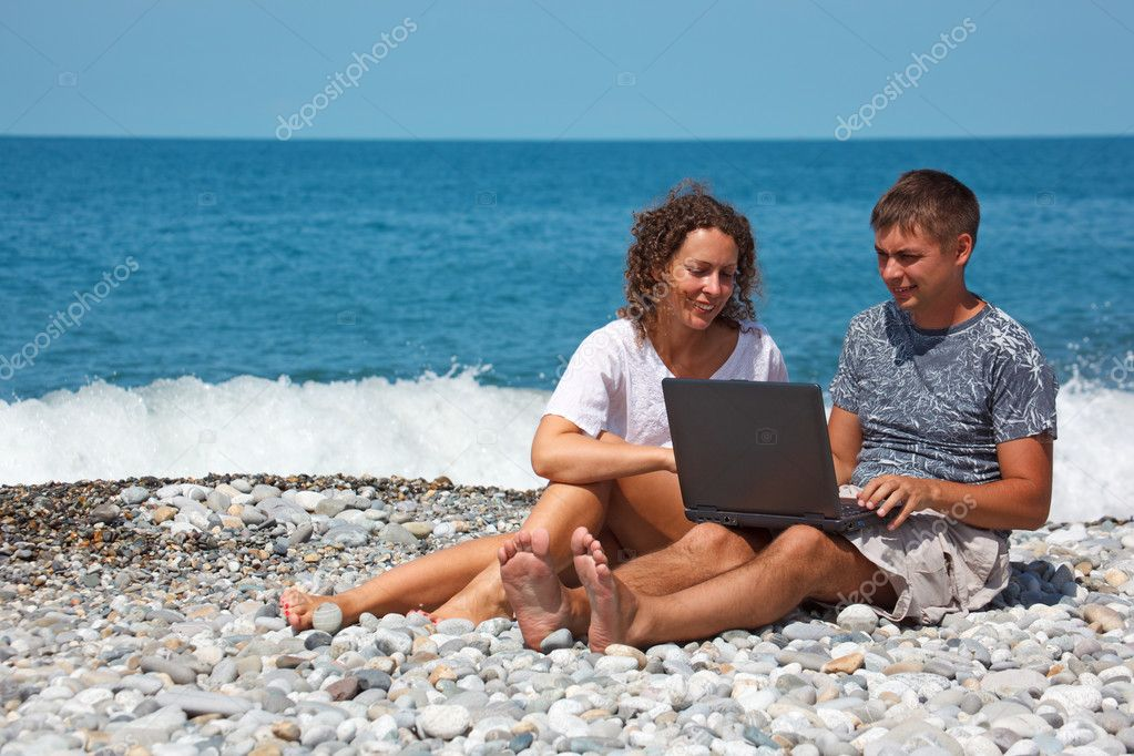 Man and girl on seashore with laptop