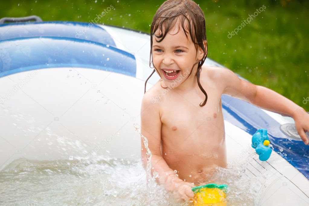 The little girl plays in inflatable pool a sunny day.