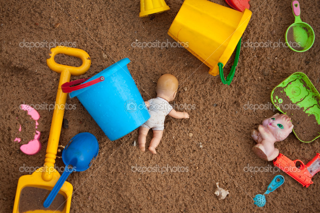 The thrown toys in a sandbox
