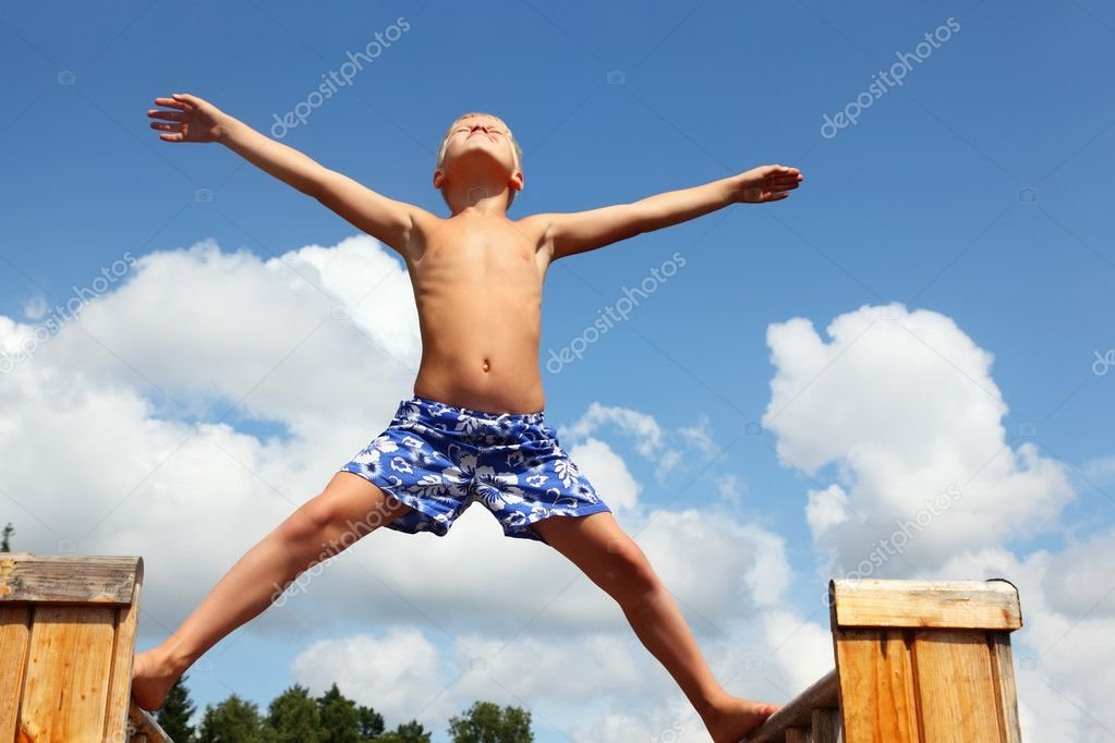 Boy in shorts standing on boards against clouds, plants hands an