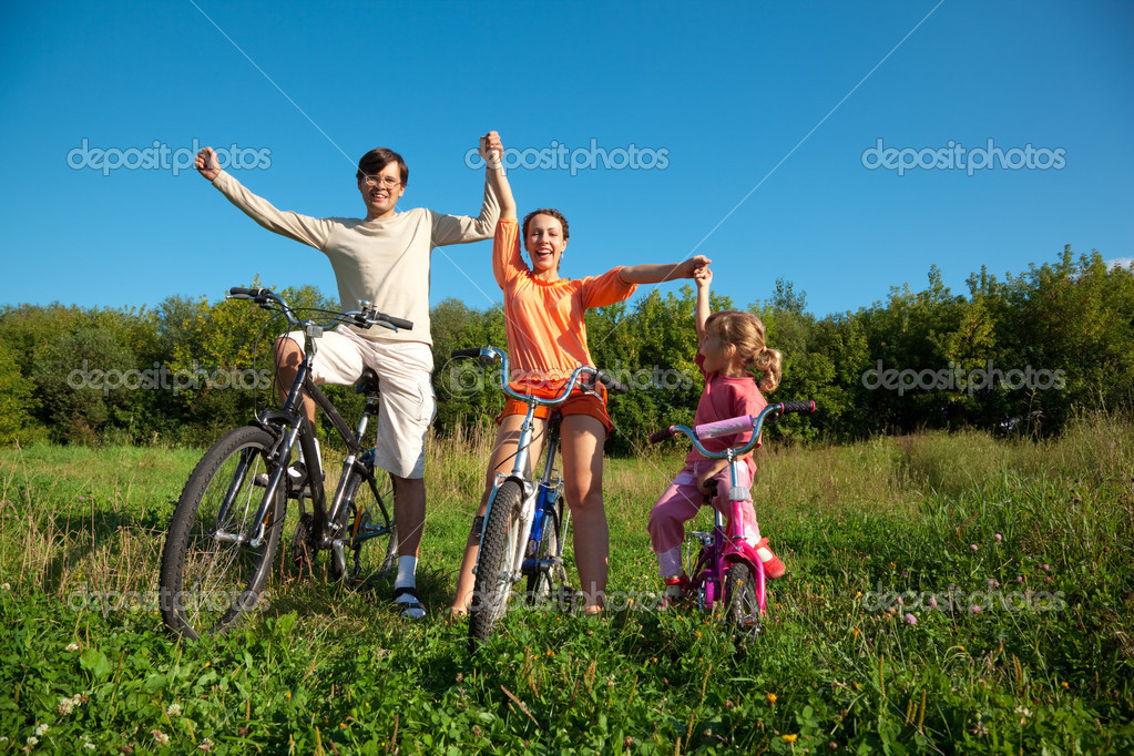Parents with the daughter on bicycles in park a sunny day. Have