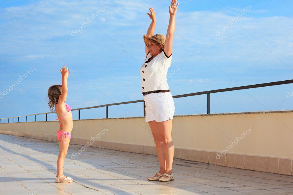 Elderly woman and little girl do morning exercise on veranda ne
