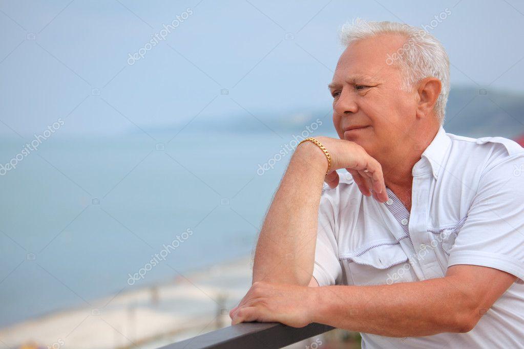 Sad senior on veranda near seacoast, looking afar, lean elbows a