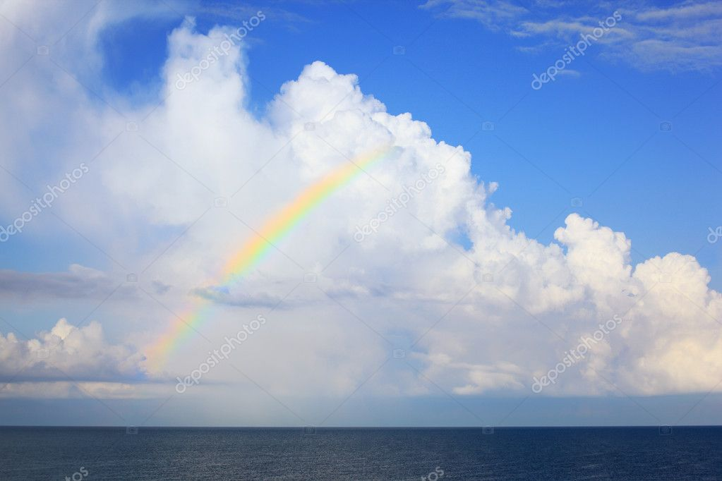White big clouds and multi-coloured rainbow over sea in afterno