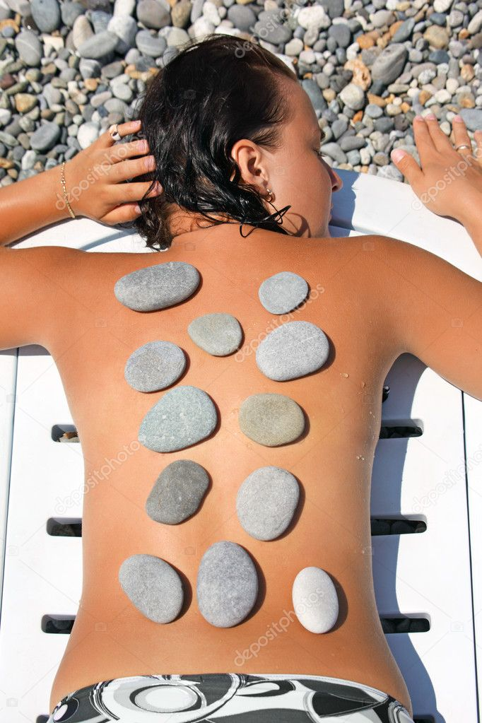 Beautiful woman sunbathes on beach with stones on back