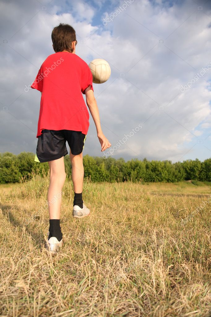 Boy with ball on meadow