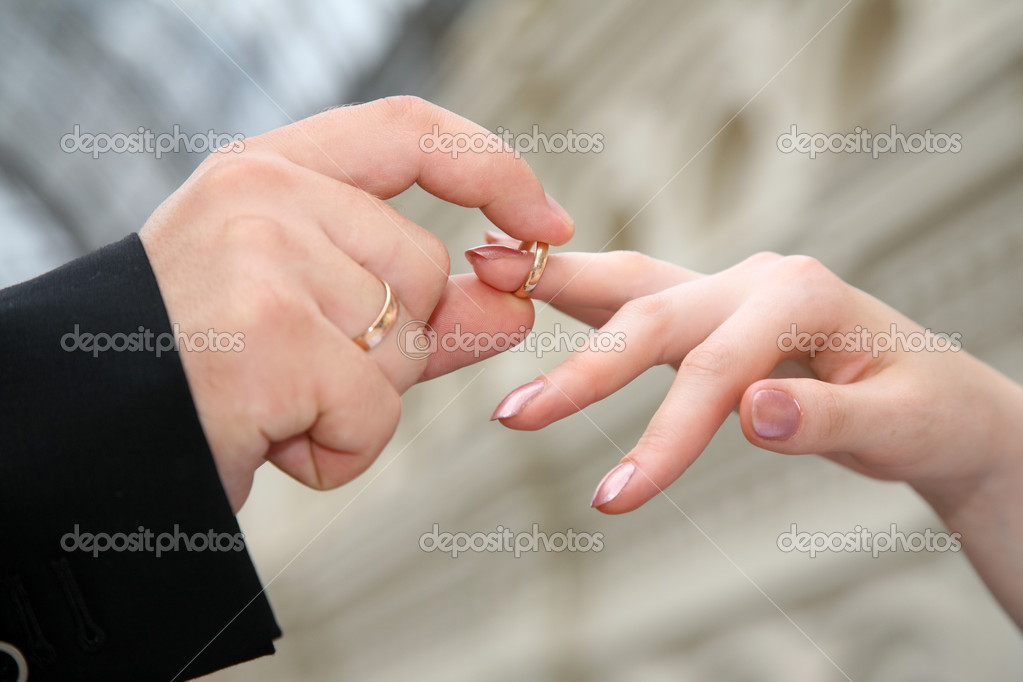 The hand, which puts on ring to another hand