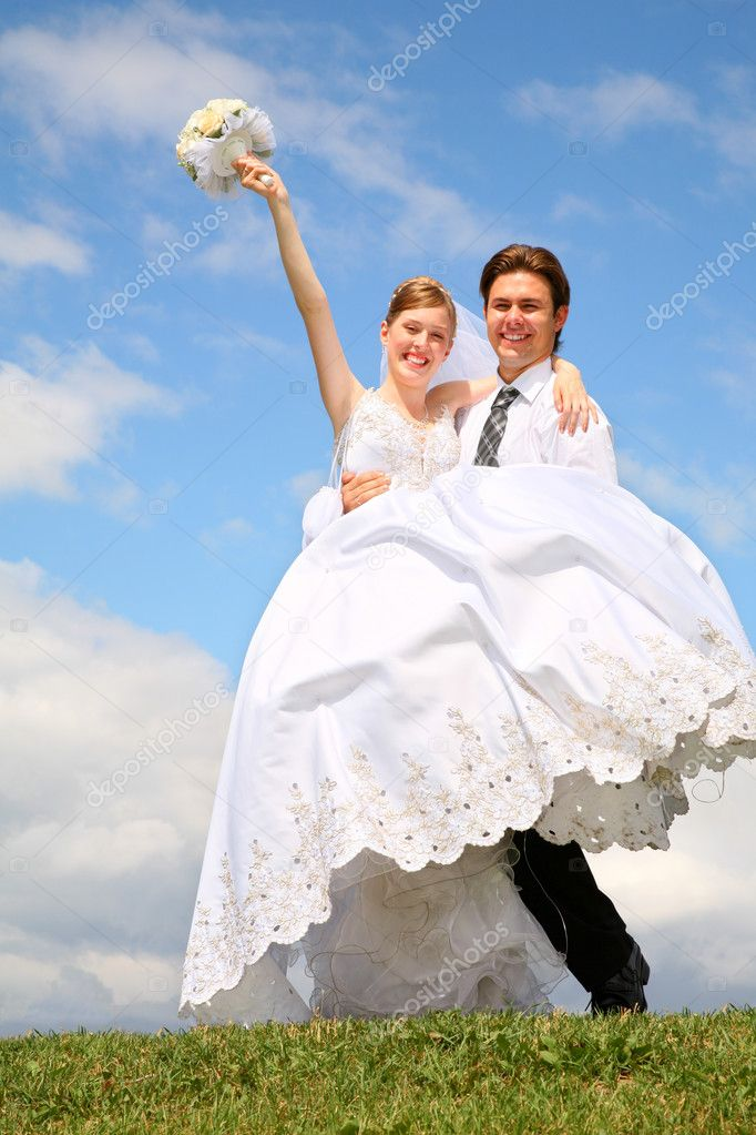 Fiance holds bride on the hands on to the meadow