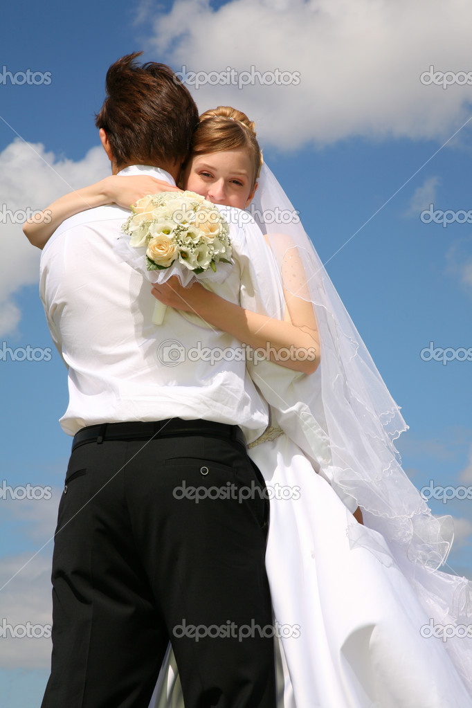 Bride embraces fiance against the background of the sky