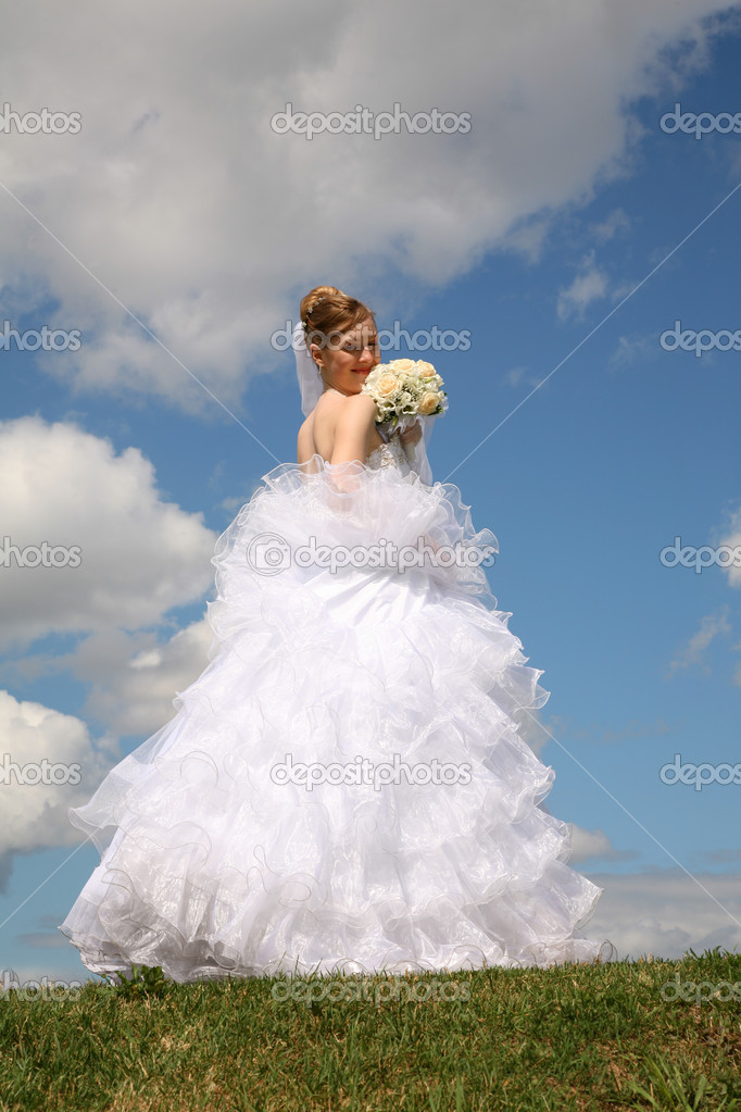 Bride stands with the bouquet on to meadow against the background of the sk
