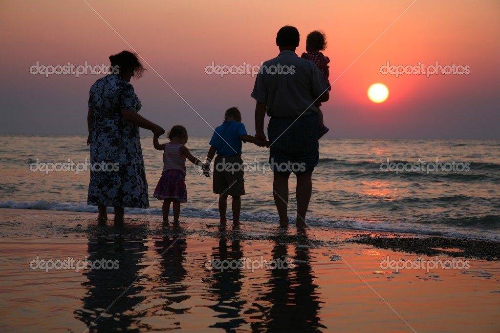 Grandfather with grandmother and the children against the background of sun