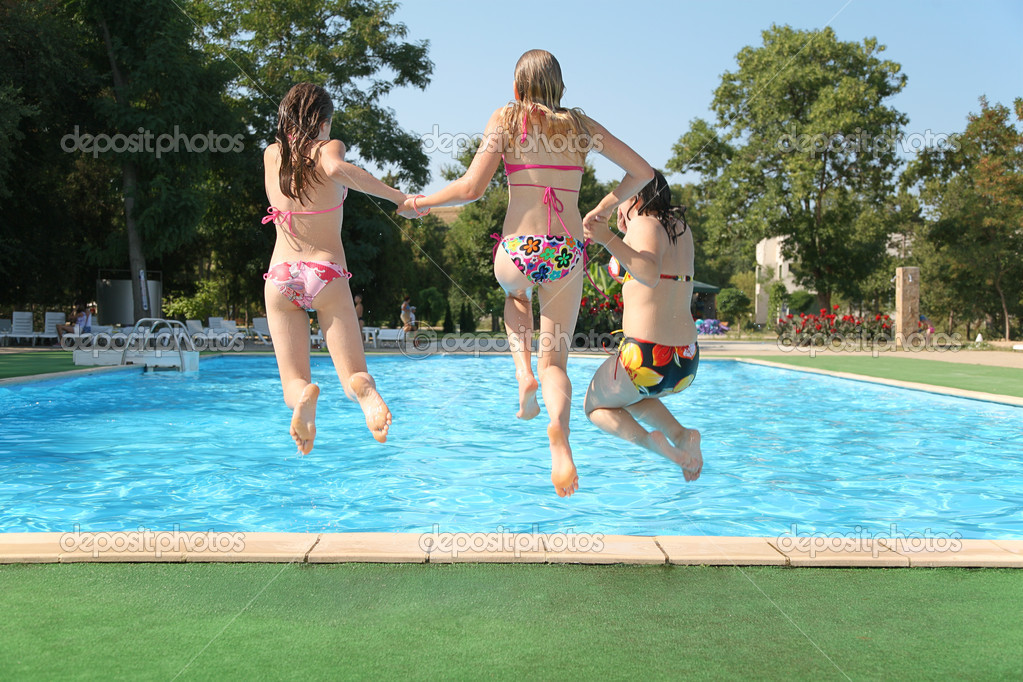 Three girls jump in pool