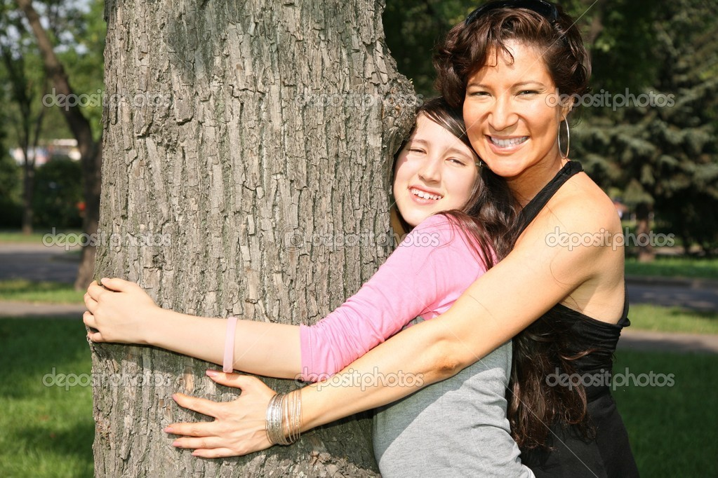 Mother and daughter embrace the tree