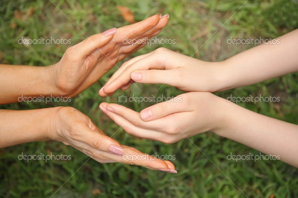 Four hands against the background of grass