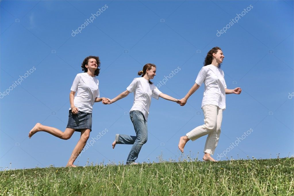 Three girlfriends in white T-shorts together run