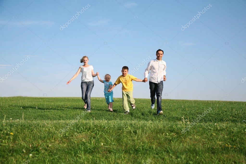 Family of four running grass sky