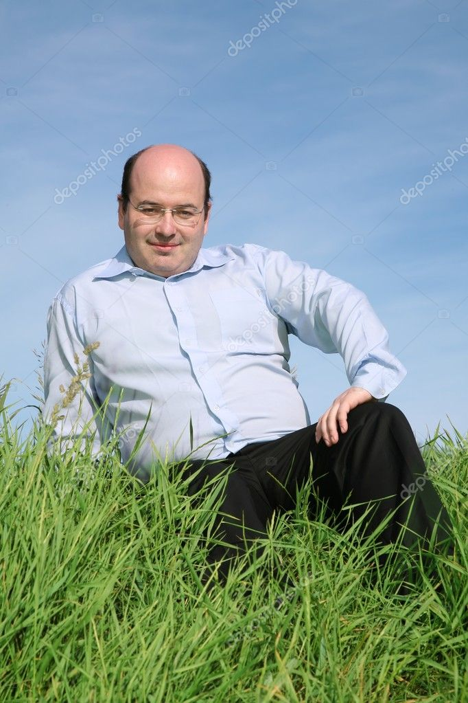 Fat man sitting grass