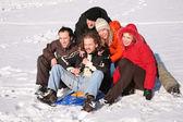 pět přátel se plastové saně sedět na sněhu