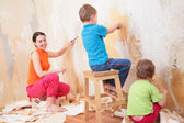 Kinder helfen Mutter, alte Tapeten zu entfernen