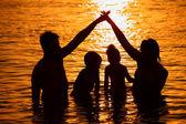 Fotografie Eltern mit Kindern im Meer bei Sonnenuntergang
