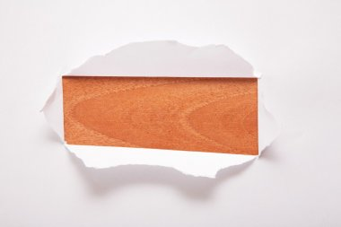 The sheet of paper with the rectangular hole against the wooden background