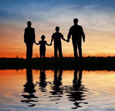 Family of four on sunset sky, water