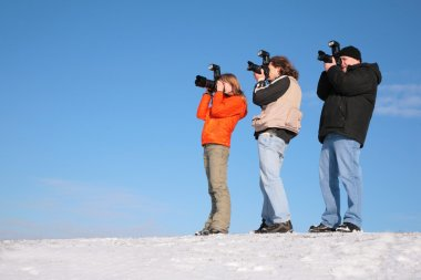 Three photographers on snow hill