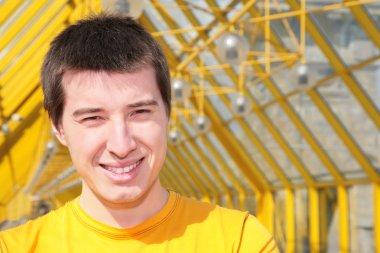 Young smiling man in yellow shirt on footbridge