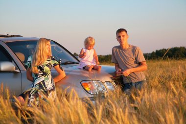 Parents and child sitting on car cowl on wheaten field