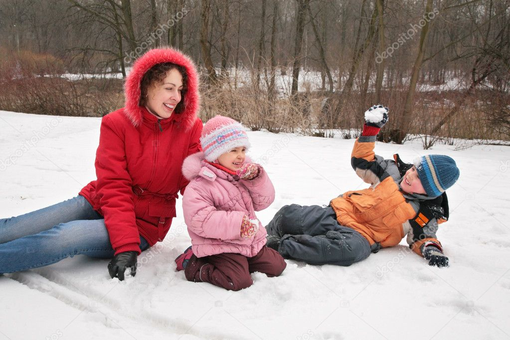 Mother and children play in winter park