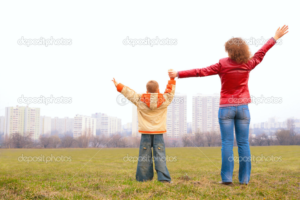 Mother and son stand outdoor with lifted hands
