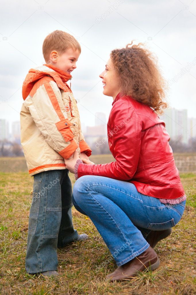 Mother and son look on each other outdoor on spring