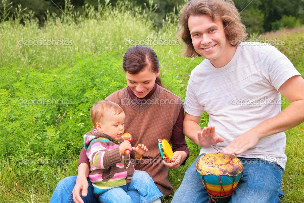 Parents and baby on nature with musical instruments