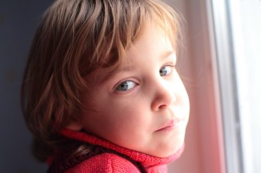 Little thoughtful girl at window