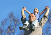Senior with child on shoulders in front of spring birch tree col
