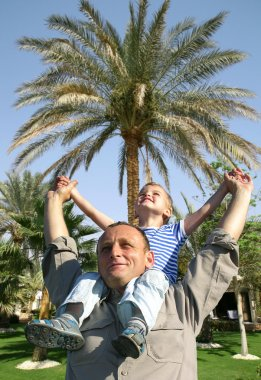 Senior with child on shoulders in front of palm tree collage