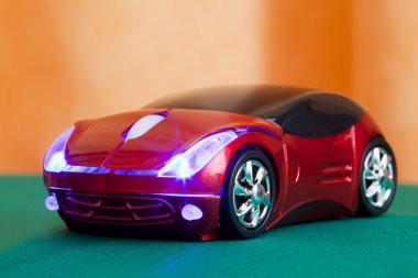 Computer mouse in form toy red sports car with glow headlights