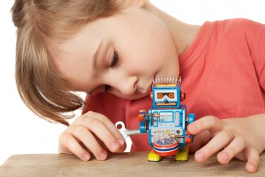 Little girl in red T-shirt plays with clockwork robot isolated o