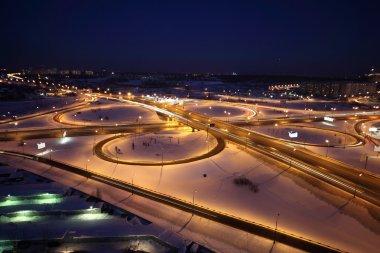 Night winter cityscape with big interchange, lighting columns an
