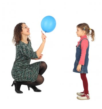 Little girl and her mother playing with blue balloon side view i
