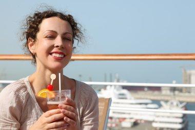 Beauty brunette woman in white shirt standing on cruise liner de