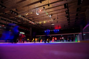 Big covered skating rink with multi-coloured illumination in spo